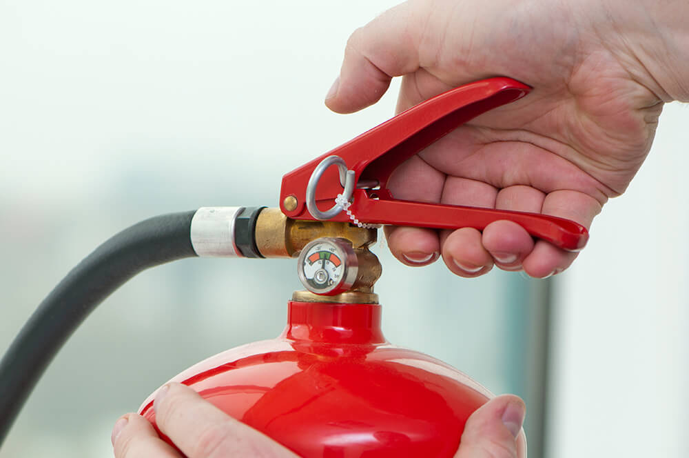 image shows a hand holding a fire extinguisher, ready to trigger